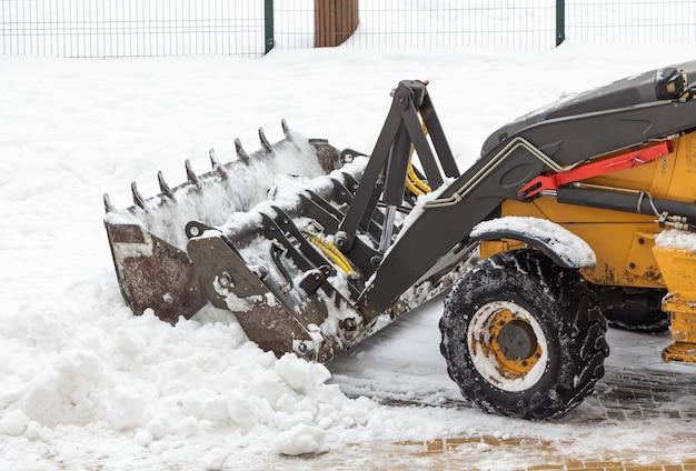 Een kleine tractor verwijdert sneeuw van de weg bij het huis.