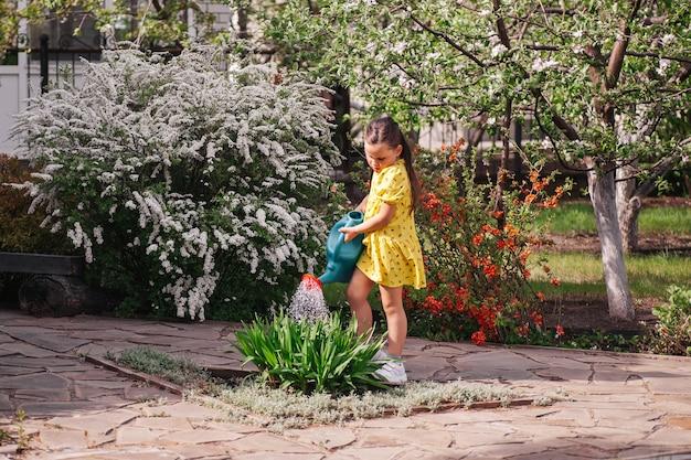 Een kleine tuinman geeft bloemen water uit een gieter, een meisje tuiniert in de achtertuin en helpt haar pa...