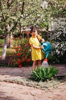 Een kleine tuinman geeft bloemen water uit een gieter een meisje tuiniert in de achtertuin in een b...