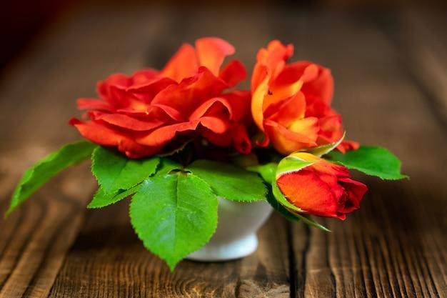 Een kleine vaas met rode rozen op een houten tafel.