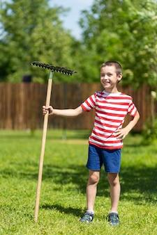 Een kleine vrolijke jongen staat en houdt een hark in zijn hand, klaar om in de tuin te werken