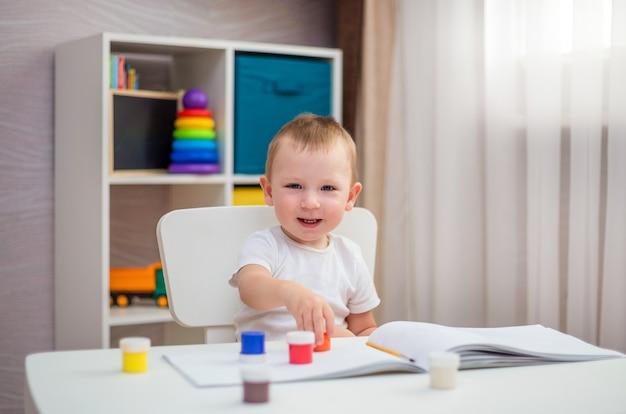 Een kleine vrolijke jongen zit aan een tafel en tekent met verf