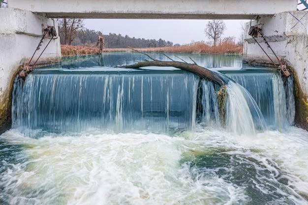 Een kleine waterval aan de rivier, een kleine dam met een drempel.