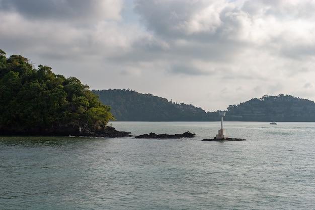 Een kleine witte vuurtoren op de stenen bij het eiland aan de rivier