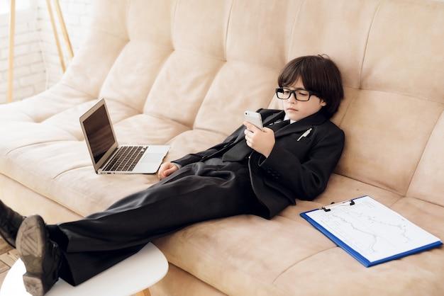 Een kleine zakenman ligt op de bank met telefoon