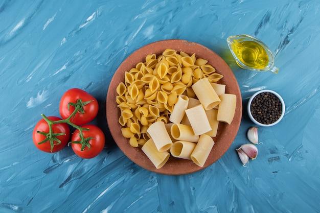 Een kleiplaat van ongekookte pasta met olie en verse rode tomaten op een blauwe ondergrond.