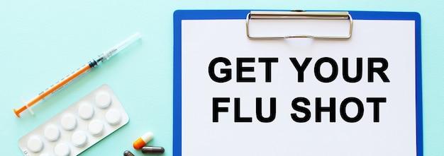Een klembord met papier ligt op een tafel in de buurt van drugs en een spuit inscriptie get your flu shot