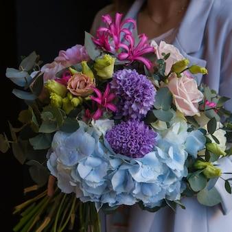Een kleurrijk boeket anjers, rozen, windbloemen en flossbloemen