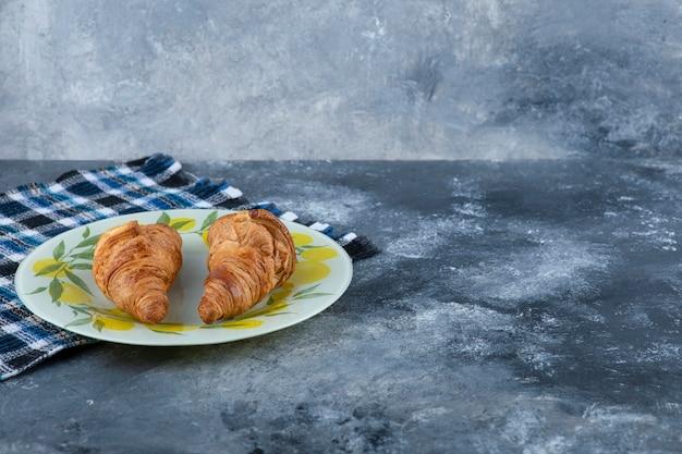 Een kleurrijk bord met verse croissants op een marmeren tafel.