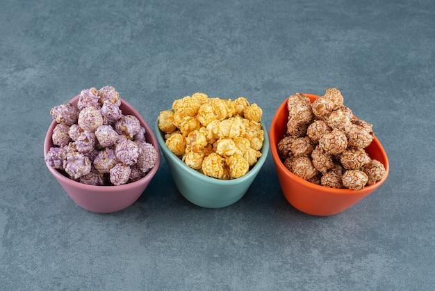 Een kleurrijk geassorteerde variëteit aan popcorn snoep smaken geassorteerd in kleine kommen op marmeren achtergrond. hoge kwaliteit foto