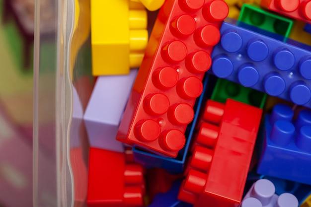 Een kleurrijke bouwset, die op de vloer van een huis ligt, close-up. educatieve spelletjes voor kinderen. plastic kinderkubussen, selectieve aandacht.