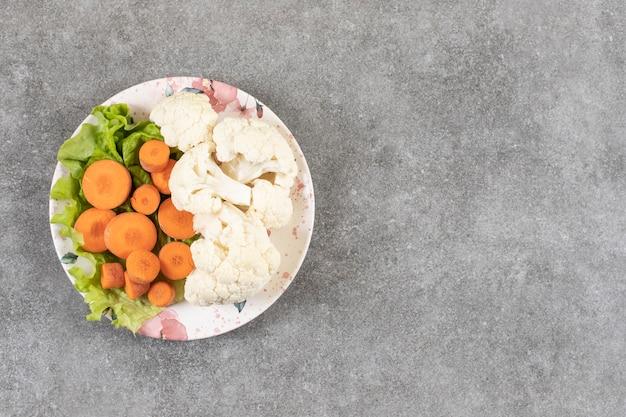 Een kleurrijke plaat van gehakte verse groenten op een stenen ondergrond.