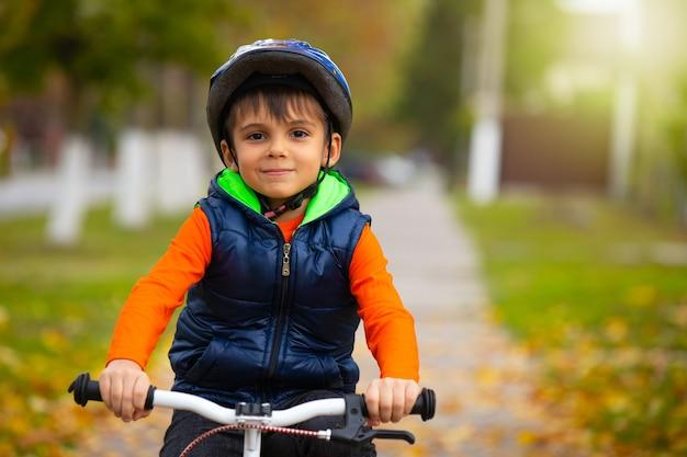 Een kleuterschooljongen die een helm draagt en op een fiets rijdt op een herfstdag. actieve gezonde buitensporten. foto met lege zijruimte.