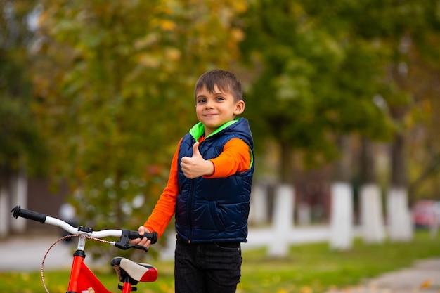 Een kleuterschooljongen in een herfstpark. een klein kind laat de klas zien. actieve gezonde buitensporten. foto met lege ruimte.