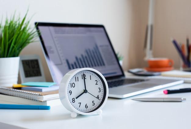 Een klok op de achtergrond van een laptop