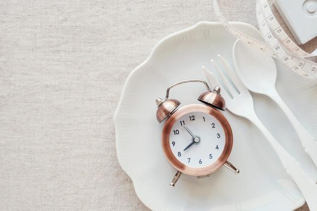 Een klok op de plaat en meetlint, intermitterende vasten dieet concept