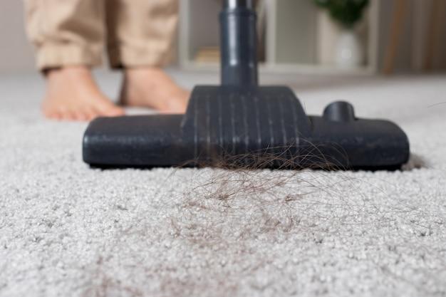 Een klomp lang haar op het tapijt en een close-up van een stofzuiger.
