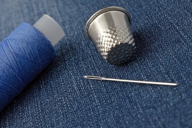 Een klosje draad met een naald en een vingerhoed. op denim achtergrond. detailopname.
