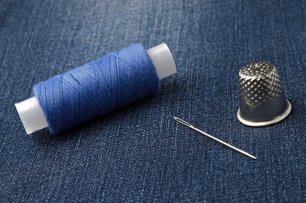 Een klosje draad met een naald en een vingerhoed. op denim achtergrond.