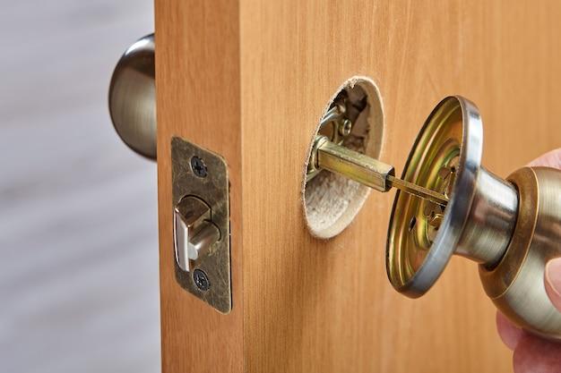 Een klusjesman verbindt twee stukken deurknop met spindel terwijl hij de handgreep met vergrendelingsmechanisme monteert.