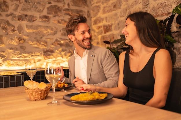 Een knap jong koppel verliefd in een restaurant, met plezier samen eten, valentijn vieren