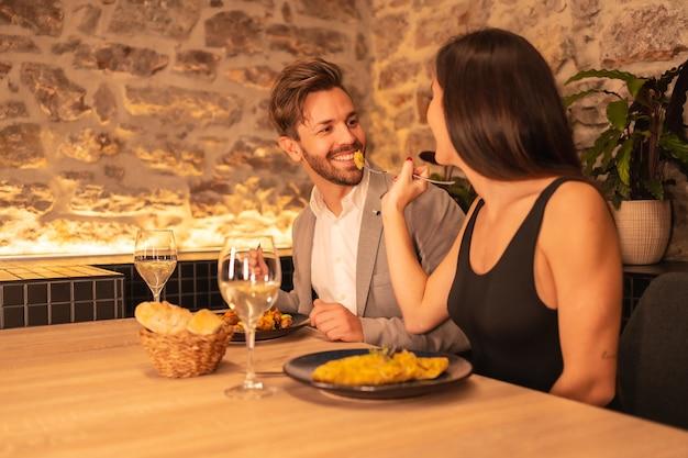 Een knap jong stel verliefd in een restaurant, met plezier samen eten