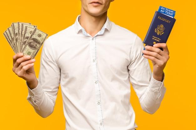 Een knappe aziatische man in een wit overhemd verheugt zich over het winnen van de loterij. hij houdt een paspoort met vliegtickets en geld dollars op een gele achtergrond. - afbeelding