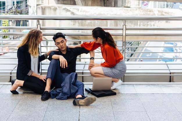 Een knappe aziatische man, thai, zit op de vloer. hij heeft een droevig gezicht en is uitgeput. er waren op het moment van troost twee vrouwelijke collega's. in het concept van werkloos of ontslagen uit werk