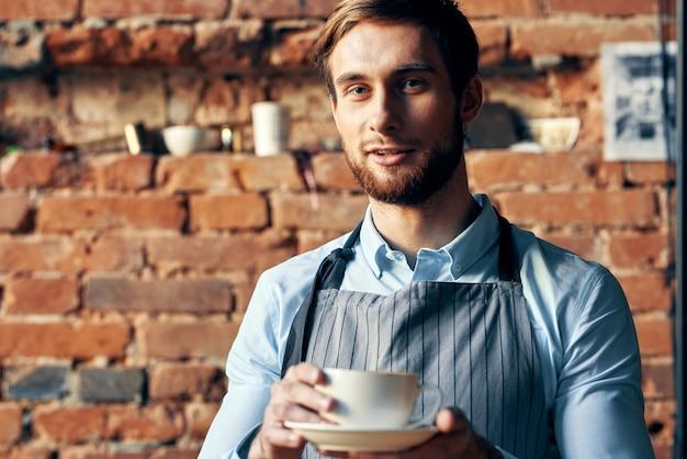 Een knappe barista die een koffiekopje vasthoudt