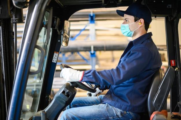 Een knappe bouwvakker besturen van een heftruck in een industriële fabriek