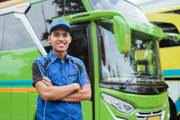 Een knappe buschauffeur in uniform en hoed glimlacht met gekruiste handen tegen de bus