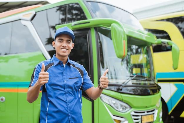 Een knappe buschauffeur in uniform en hoed glimlacht met zijn duimen tegen de bus