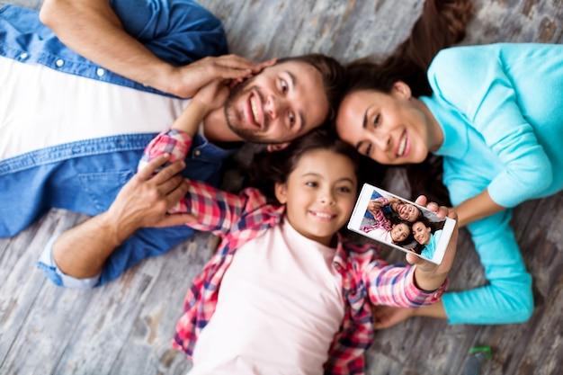Een knappe familie van drie personen ligt op de grond, vermaakt zich en maakt een selfie op hun nieuwe smartphone