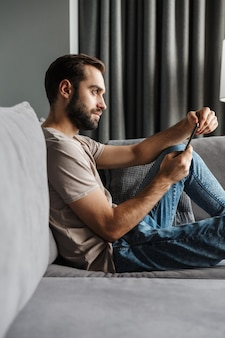 Een knappe geconcentreerde jonge man binnenshuis thuis op de bank chatten via de mobiele telefoon.