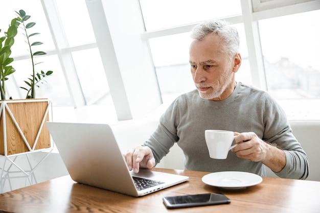 Een knappe geconcentreerde volwassen senior zakenman zitten in café met behulp van laptopcomputer koffie drinken.
