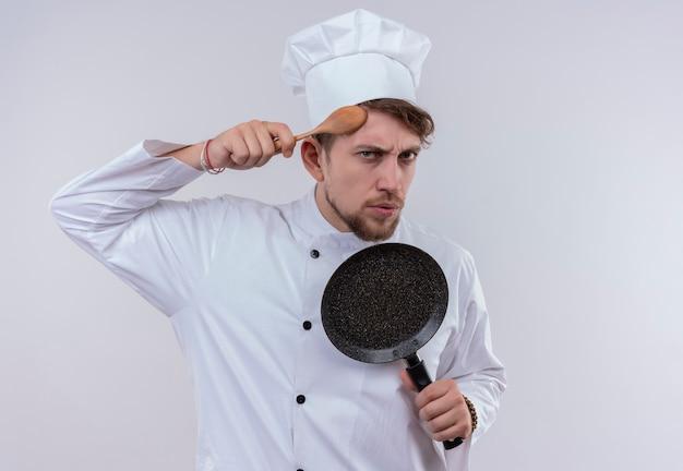 Een knappe jonge bebaarde chef-kok man met wit fornuis uniform en hoed met koekenpan terwijl hij houten lepel op zijn hoofd op een witte muur houdt