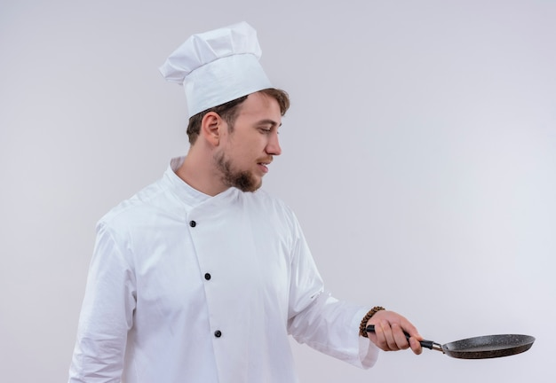 Een knappe jonge, bebaarde chef-kokmens die witte eenvormige fornuis en hoed draagt die koekenpan op een witte muur bekijkt
