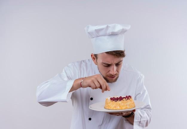 Een knappe jonge, bebaarde chef-kokmens die witte uniforme fornuis en hoed draagt die een plaat met cake op een witte muur aanraakt