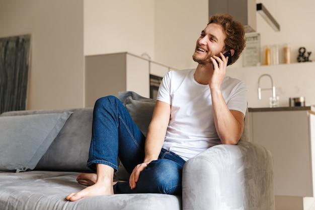 Een knappe jonge bebaarde man op de bank thuis praten via de mobiele telefoon.