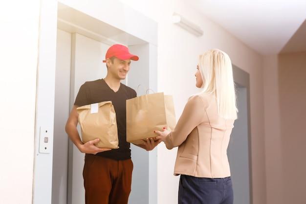Een knappe jonge bezorger die een pakket aflevert bij het appartement