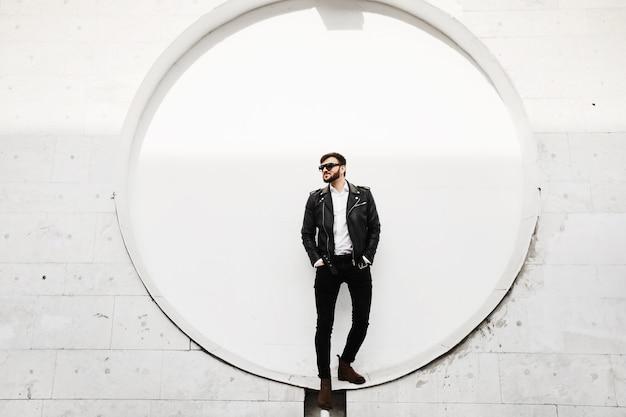 Een knappe jonge brute mannen, stijlvolle en modieuze man met baard, in leren jas, zwarte spijkerbroek en zwarte zonnebril, poseren in de zonnige straat voor de witte muur van het gebouw