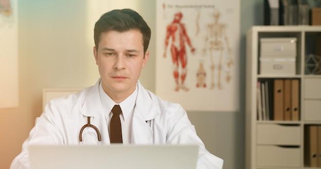 Een knappe jonge dokter met geeft online consult met behulp van laptop