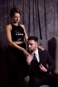 Een knappe jonge man in een pak zit in een stoel en houdt de hand van een mooie vrouw in een zwarte avondjurk