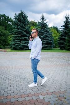 Een knappe jonge man van europees uiterlijk die een zonnebril draagt, is gekleed in een shirt en spijkerbroek. de man loopt over straat, hij is stijlvol gekleed