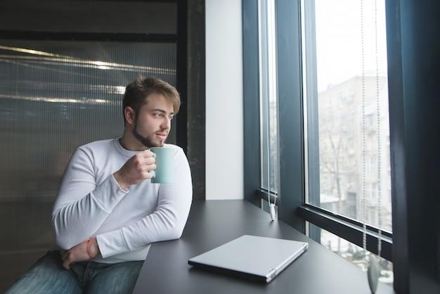 Een knappe jonge man zit aan een tafel met een kopje koffie in de buurt van een gesloten laptop