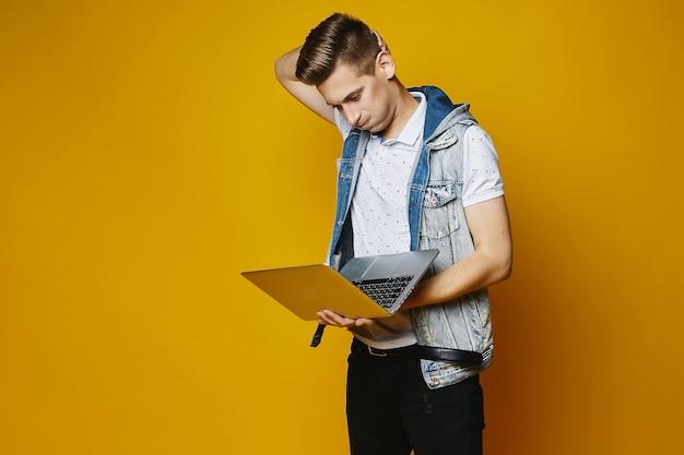 Een knappe jonge mannen, stijlvolle en modieuze mannen met trendy kapsel, in wit t-shirt, in spijkerbroek en in jeans vest, met mode-ruimte grijze laptop in zijn handen poseren op gele achtergrond