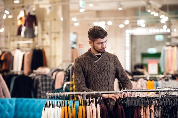 Een knappe jonge mens die kleding in een detailhandel kiest