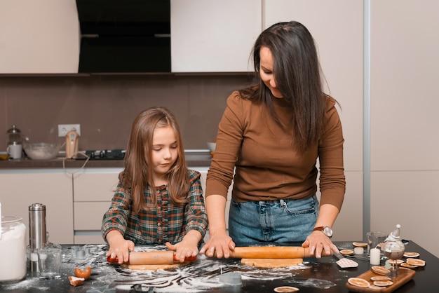 Een knappe jonge moeder met haar dochter maakt thuis koekjes met een leuke tijd in de keuken