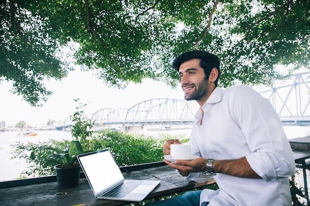 Een knappe jonge zakenman die met laptop werkt en koffie drinkt op boomkoffie met brugachtergrond