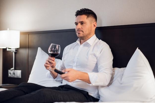 Een knappe jonge zakenman met een glas rode wijn in bed